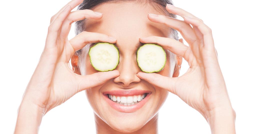 vrouw houdt komkommers voor de ogen